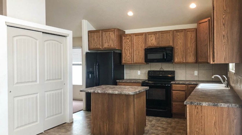 The kitchen of 165 Winter Hawk includes appliances, a center island with eating space, and a pantry.