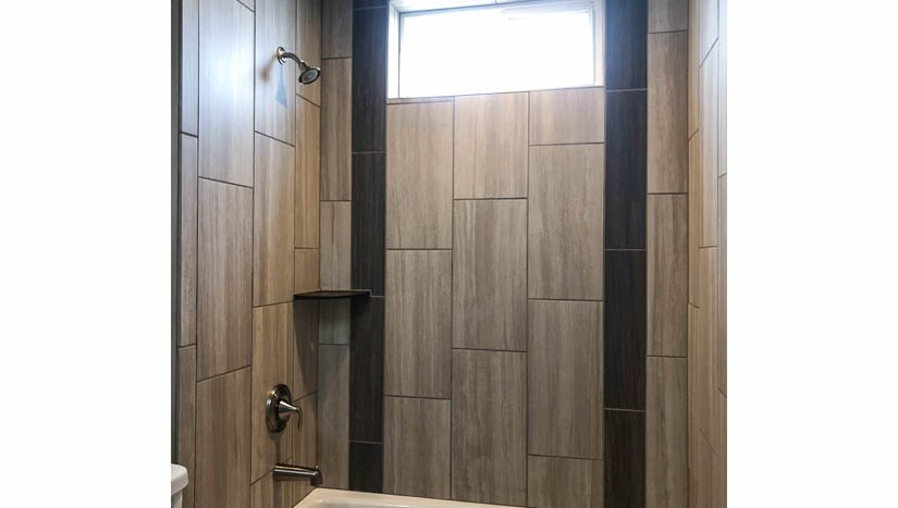 The hall bath has a custom tiled in=tub shower with an operable window.