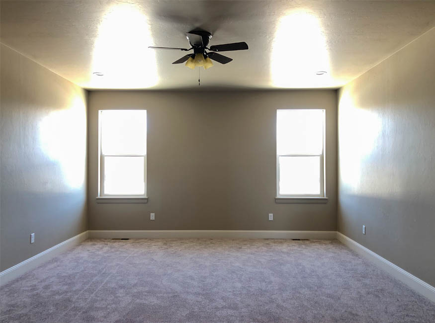 The master bedroom of 853 Fire Agate has east facing single hung windows, recessed lighting, and a lighted ceiling fan.
