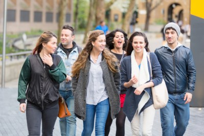Group of friends walking and having fun together in London. They are four girls and two boys in their twenties, friendship and lifestyle concepts, autumn clothing