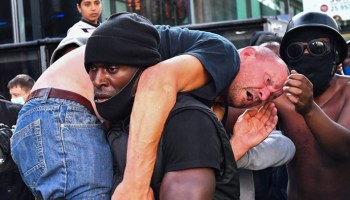 Black protester carries white man through angry crowd to safety to 'stop someone from being killed'