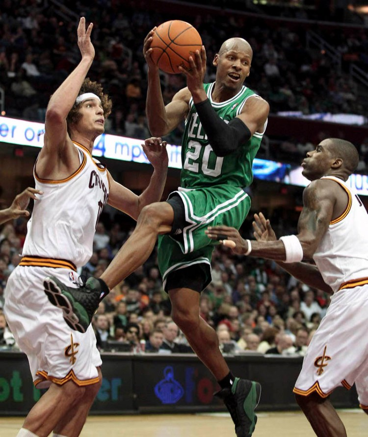 Boston Celtics' Ray Allen (top) looks to make a pass while defended by Cleveland Cavaliers' Anderson Varejao (L) and Antawn Jamison (R) during the third quarter of their NBA basketball game in Cleveland January 31, 2012. REUTERS/Aaron Josefczyk (UNITED STATES - Tags: SPORT BASKETBALL)