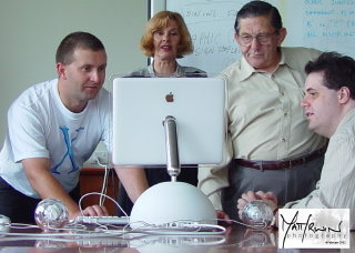Luke, Susan, Ron and Nicholas looking at iMac screen. Photo shows rear of iMac.