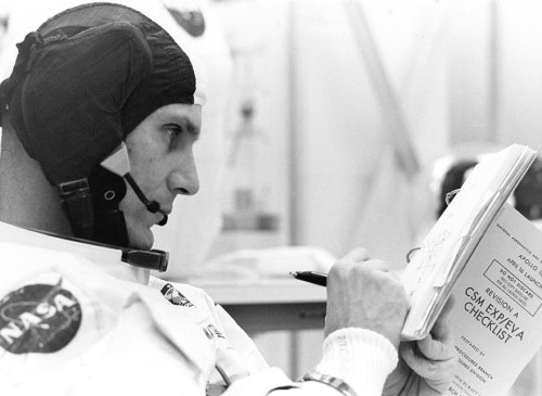 Ken Mattingly makes notes in his flight checklist while undergoing spacesuit pressure checks for the Countdown Demonstration Test.