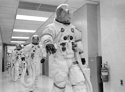 Jim Lovell leads Fred Haise and Jack Swigert to the transfer van.