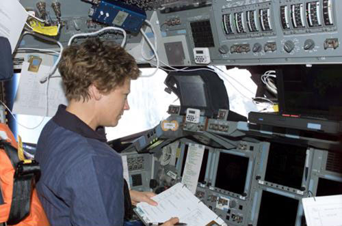 STS-114 Commander astronaut Eileen M. Collins goes over a check list dealing with rendezvous and docking operations.