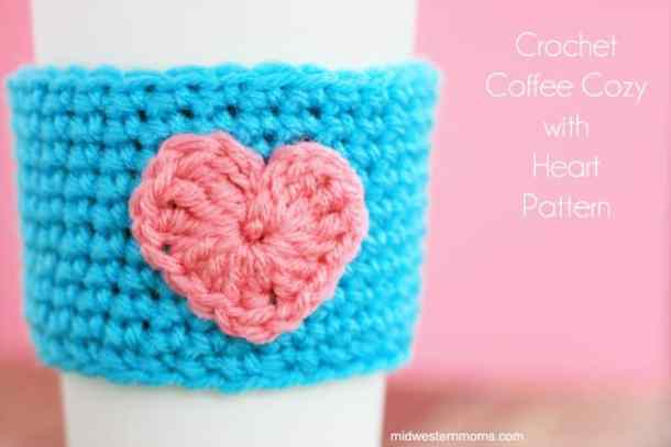 Crocheted blue mug cozy with pink heart in front of a pink surface