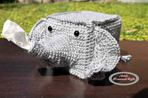 Crocheted Tissue box cover as a grey elephant with tissues coming out of his trunk sitting on a wooden table on grass