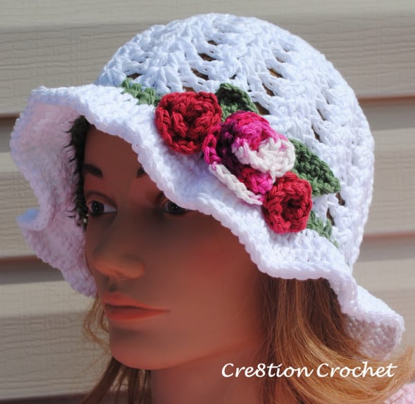 Crocheted white hat with flowers worn by a mannequin in front of a wooden background