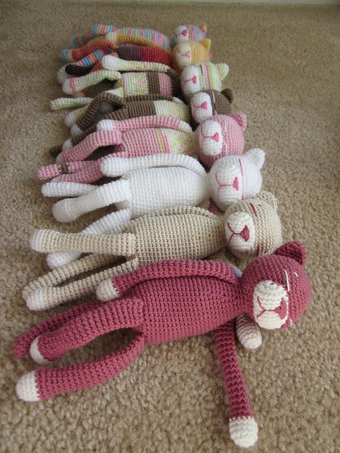 8 crocheted sleeping colorful cat amigurumis on a brown carpet