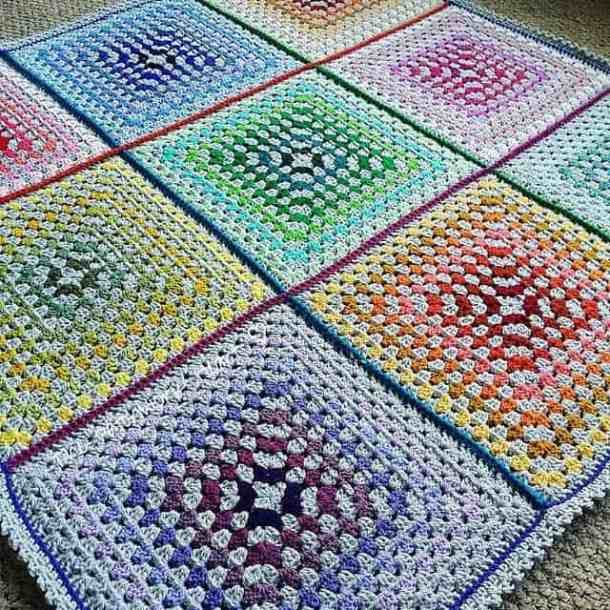 Crocheted colorful rainbow-like Granny Square blanket with 9 squares each having a different color laying on beige carpet