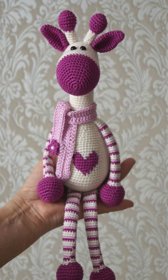Crocheted Purple Giraffe with a heart on its belly sitting on a hand