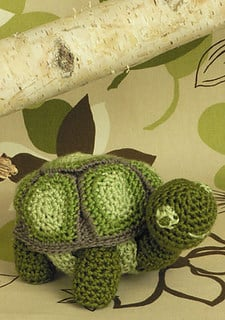 Crocheted green Turtle sitting on a leave textured background with a tree branch