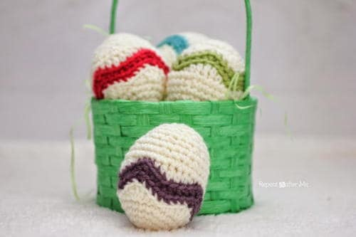 Chevron Easter Eggs that are decorated with a zig zag purple, green, red or blue line displayed in a green basket on a white surface.