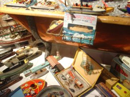 antique wooden bathtub filled with fake bubbles, models ships, surrounded by more model ships