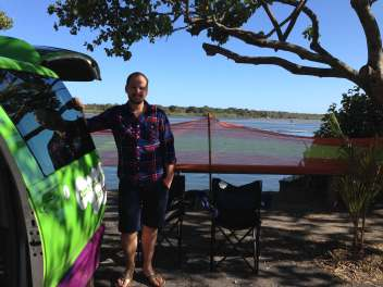 Matt stood by the campervan overlooking the river at Noosa River Holiday Park