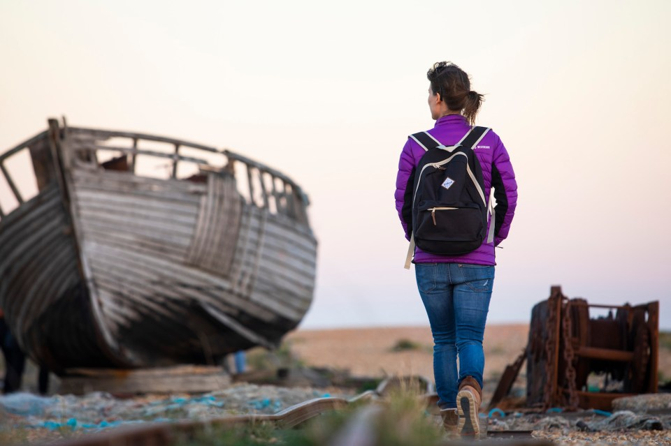 An image of myself walking past an old boat on the beach at Dungeness