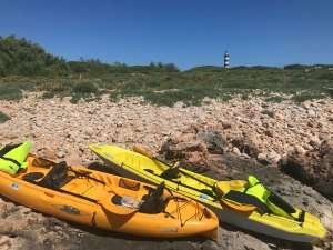 Our kayaks on Illa de l'Aire, Menorca with the lighthouse behind