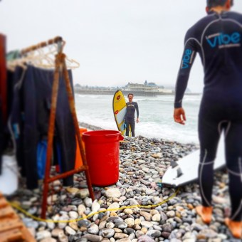 An image of myself on the beach with a surfboard in Lima, Peru.