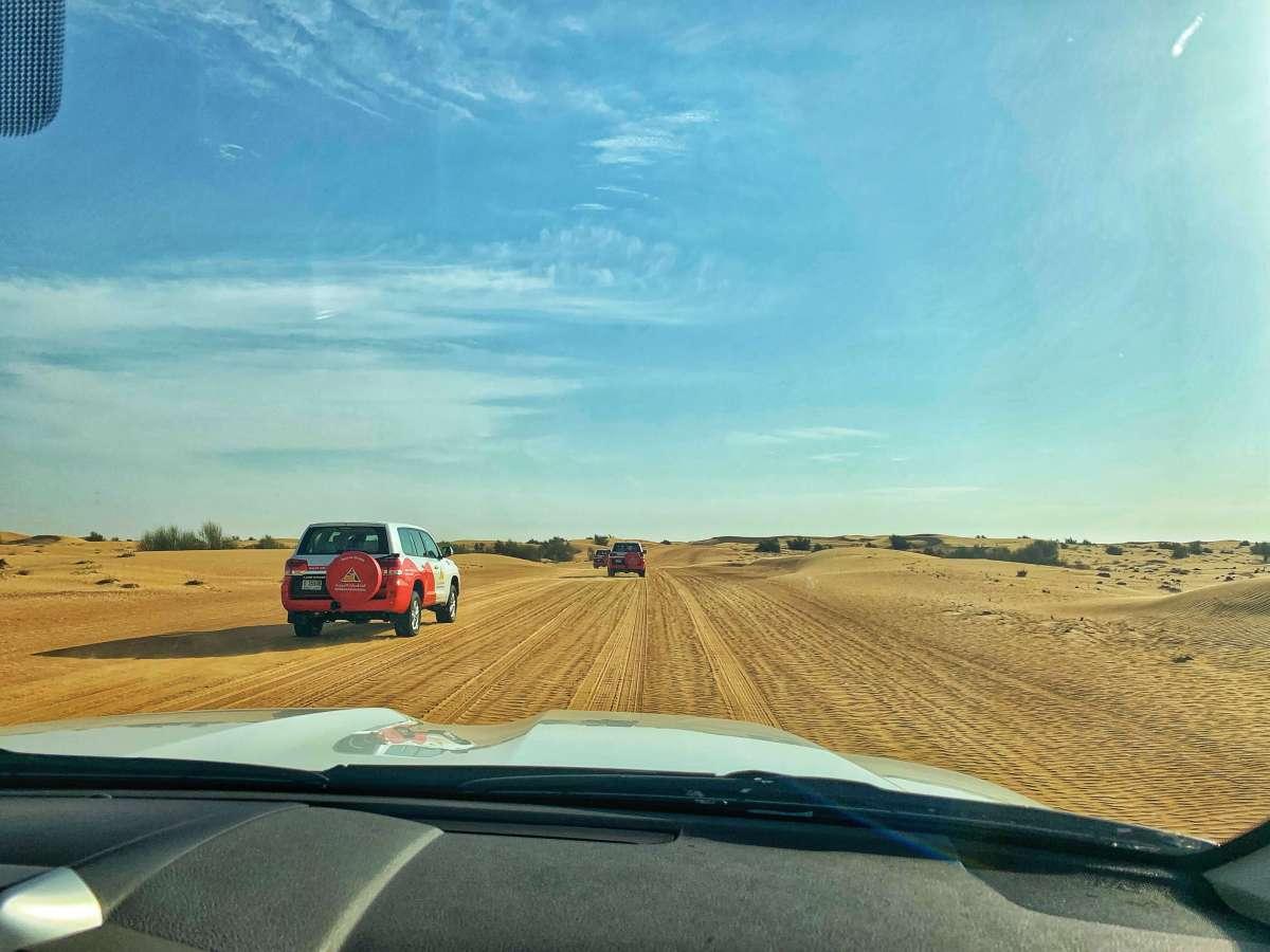 Following 4x4 vehicles on a desert safari in Dubai