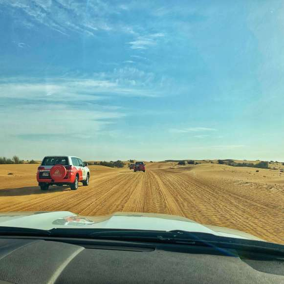 Following 4x4 vehicles on a desert safari in Dubai