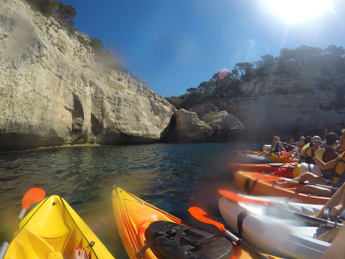 Kayak line up with the caves in the background in Menorca