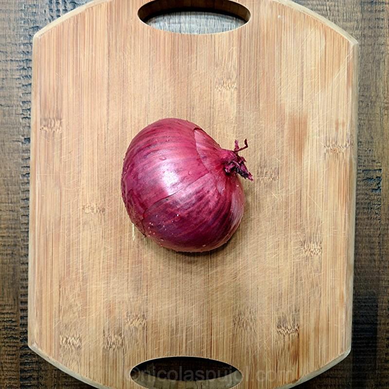 raw red onion on cutting board