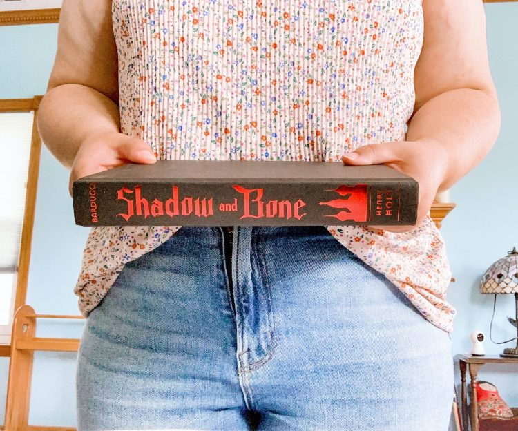 I'm wearing a floral shirt and jeans and holding the book 'shadow and bone' with the spine showing.