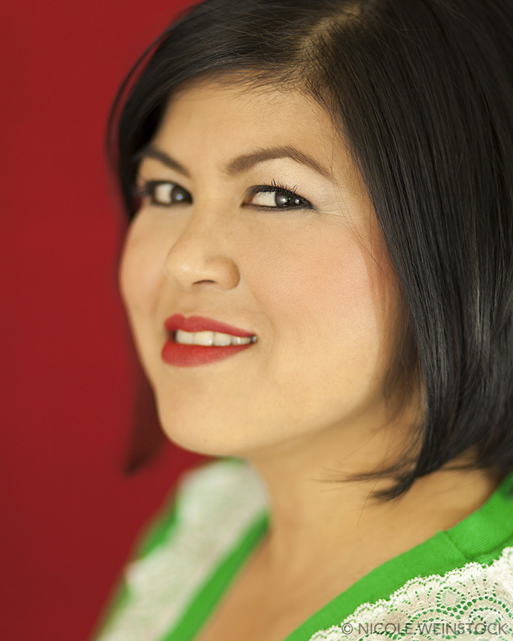 Headshot of young actress smiling mischievously from the side against a red backdrop in a green lace sweater