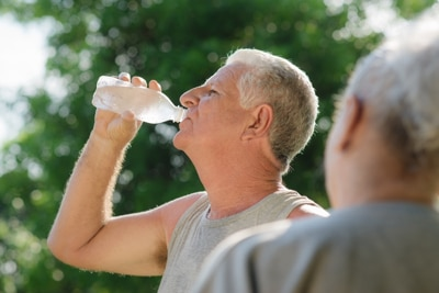 Photo of a man outside drinking bottled water - La diabetes Tipos y prevención de enfermedad