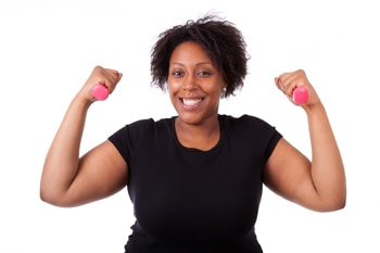 Photo of a smiling woman holding hand weights - La diabetes Tipos y prevención de enfermedad