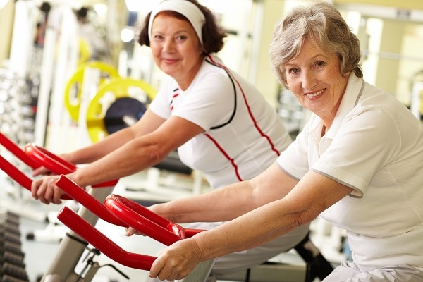 Photo of two smiling middle aged women on exercise bikes - La diabetes Tipos y prevención de enfermedad