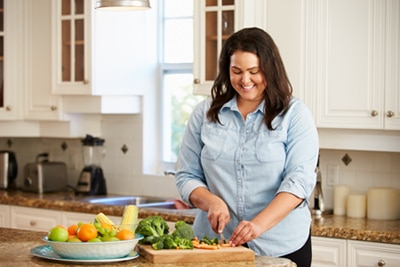 A smiling young woman chopping vegetables in her kitchen