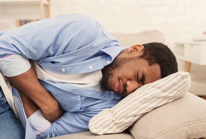 Un hombre que hace muecas de dolor mientras está acostado en un sofá.