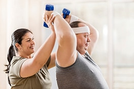 A man lifting weights with a woman providing support