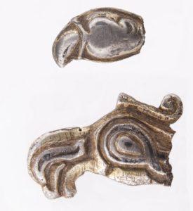 Główki ptaków drapieżnych – fragmenty wczesnośredniowiecznych trzewików pochew mieczy, znalezione na stokach grodziska w Szurpiłach. Fot. M. Bajkowska