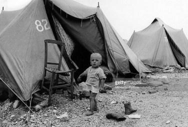 Vaikas, išgyvenęs drebėjimą vaikšto basas laikinoje stovykloje prie Camporeale. 1968 m.