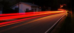 Foto met lange belichting, te zien zijn de rode strepen van de achterlichten van een voorbijrijdende auto. Copyright foto Jeff Dutton.