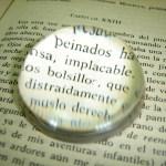 Een boek, waar een loep op ligt waardoor enkele (spaanse) woorden meer nadruk krijgen. Copyright foto: diego medrano.