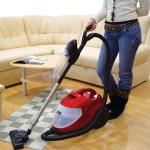Vrouw stofzuigt woonkamer. Copyright foto: Muris Kuloglija Kula