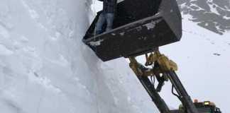 Un operario mide la altura de la nieve desde la pala de una grúa