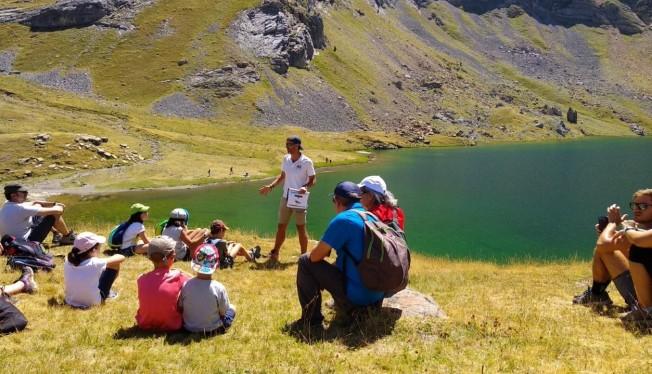 Lo senderistas atienden a las explicaciones del guía de montaña