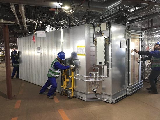 Workers move one of STENA ESTRID's prefabricated cabin units into place. AVIC Weihai.