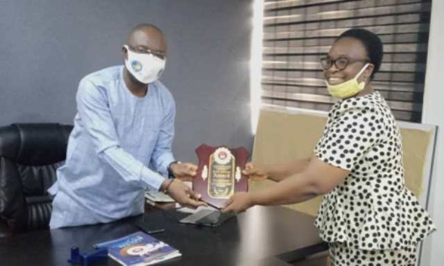 The Honourable Commissioner Youth Development, Comrade Ifeanyi Egwunyenga receiving the Youth Influencer award from the CEDESA Initiative CEO, Mrs Ugbe Iyabo Oluronke during the courtesy call to the commissioners' office