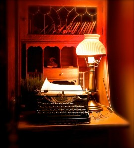 A softly lit writing desk with typewriter, lamp, and desk hutch.
