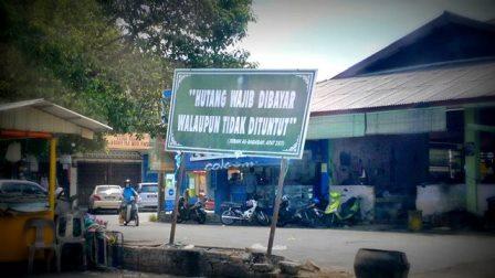 Papan peringatan - Hutang wajib dibayar di Pasar Melor