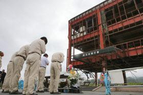 防災対策庁舎前で犠牲者の冥福を祈る復興工事の関係者たち(2014年9月11日、宮城県南三陸町)