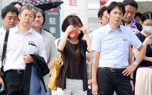 汗を拭いながら信号待ちをする人も(31日午前、東京・丸の内)
