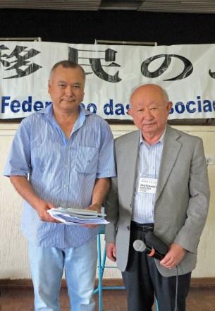 本橋団長から記念品を渡されたジュンケイロポリス・スポーツクラブ会長の矢野直茂会長(左)