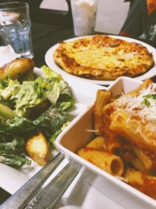 A hearty, Italian spread at Aglio e Olio. Pasta bowl, caesar salad, and pizza.